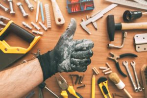 Handyman gesturing thumb up as confirmation hand sign, top view